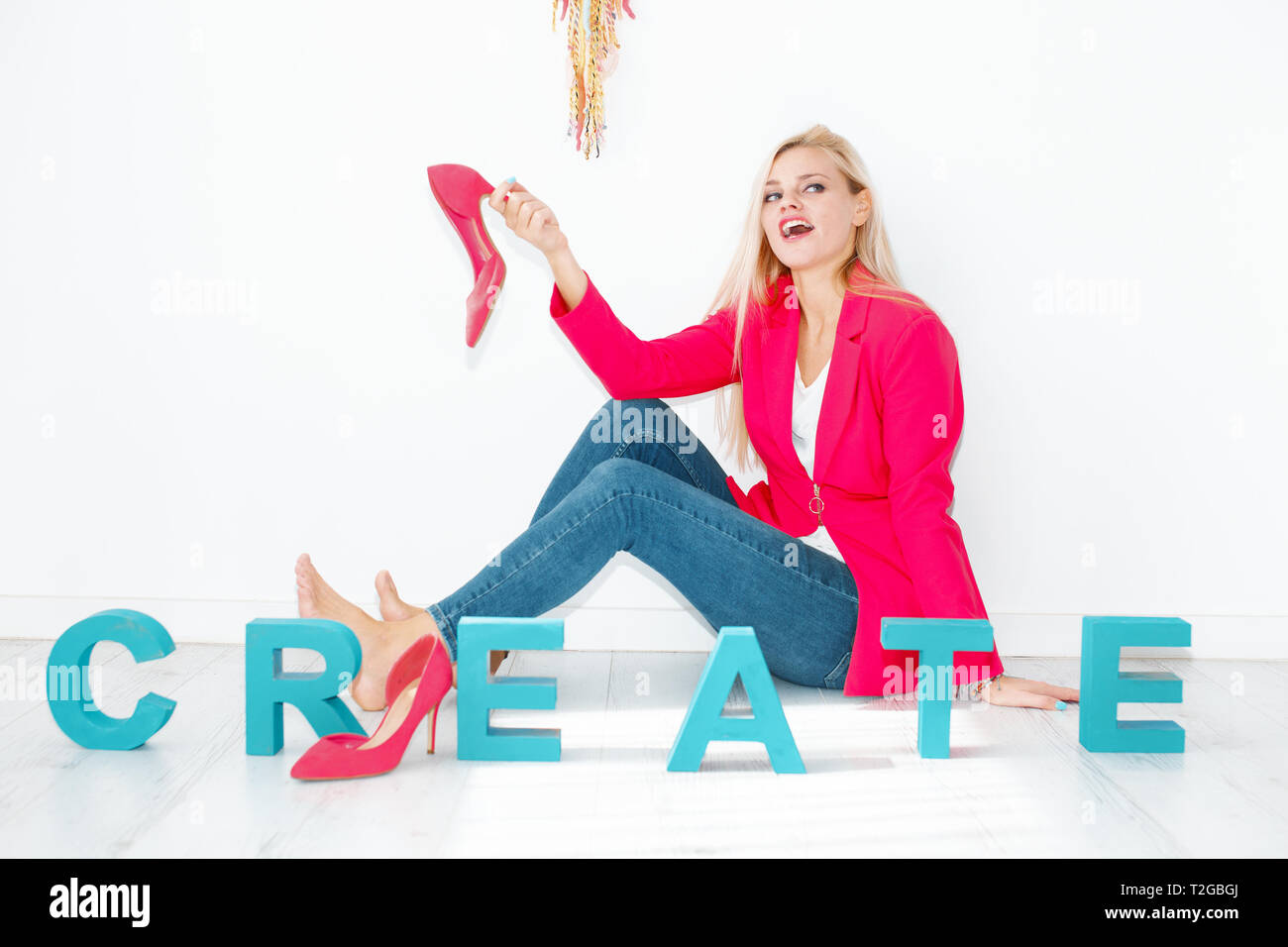 Happy young creative blonde woman holding high heels at home - Stock Image