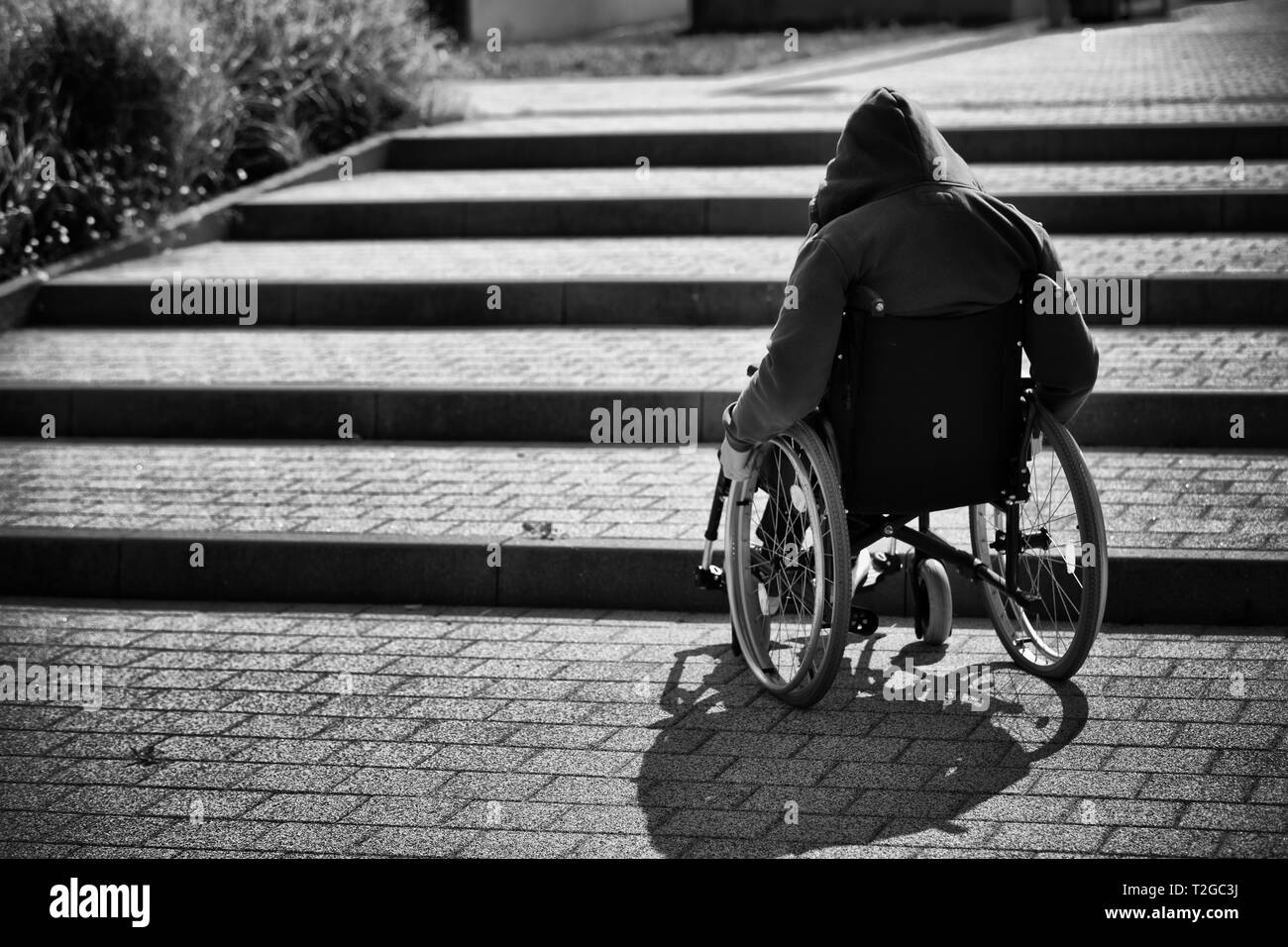 hooded man on wheelchair trying to climb up the stairs, back view - Stock Image
