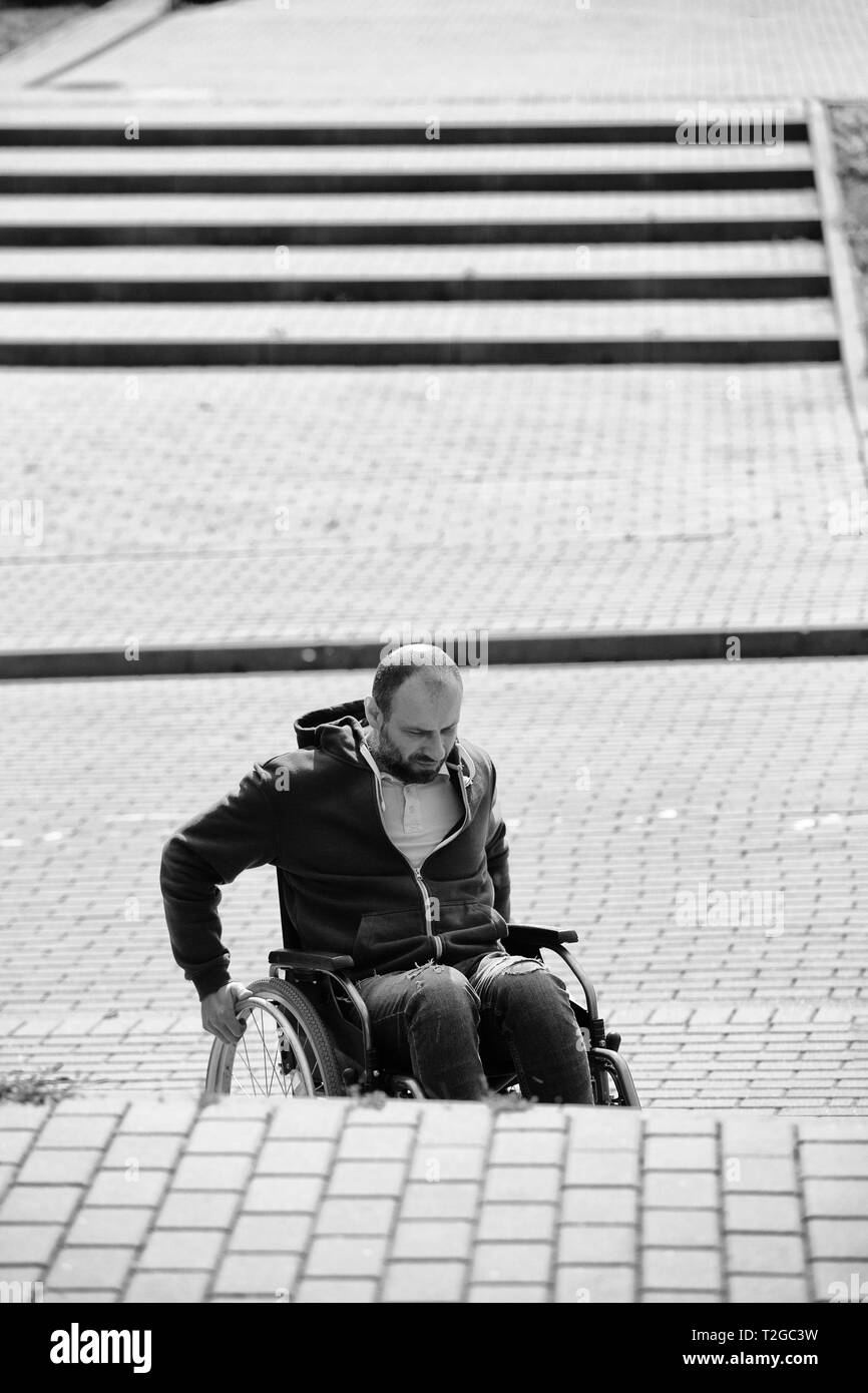 man on wheelchair trying to climb up the steps, black and white - Stock Image