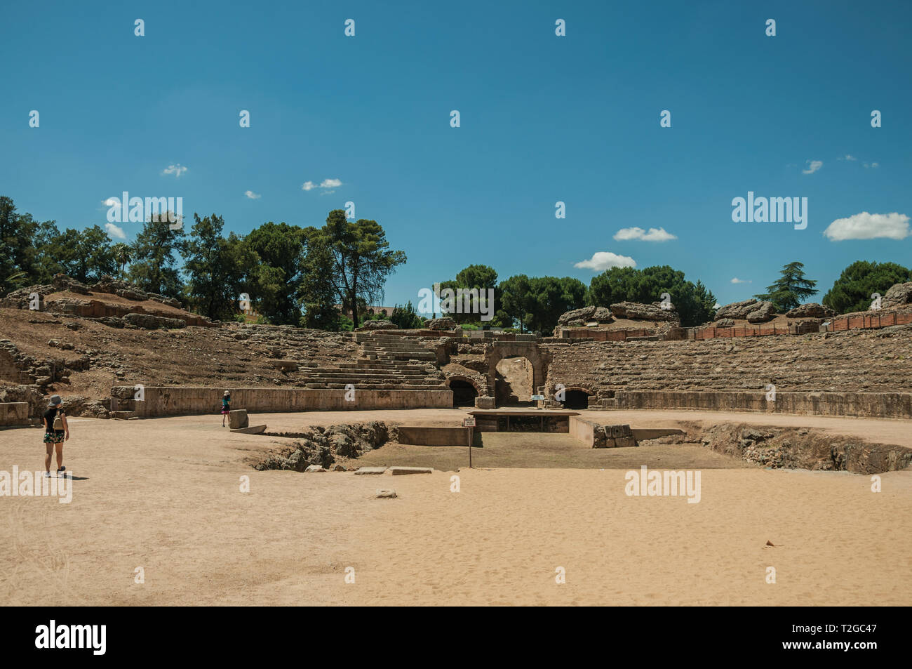 People walking around the arena of Roman Amphitheater in a sunny day at Merida. The city preserves many buildings of ancient Rome in Spain. - Stock Image