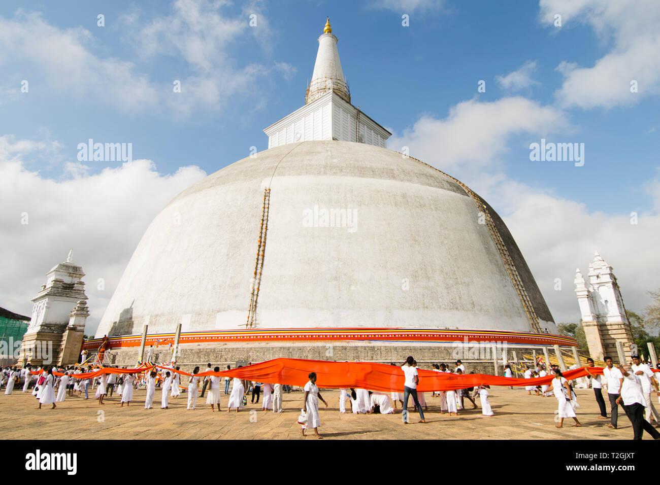 ANURADHAPURA, SRI LANKA - 21 Feb 2016: A procession of people dressed in white wraps a 366 meter-long orange cloth around the Ruwanwelisaya stupa for  - Stock Image
