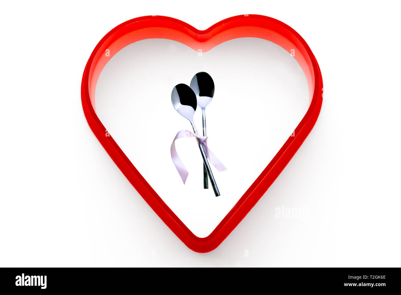 Two spoons tied together with pink ribbon.On a white background, surrounded by a red heart. - Stock Image