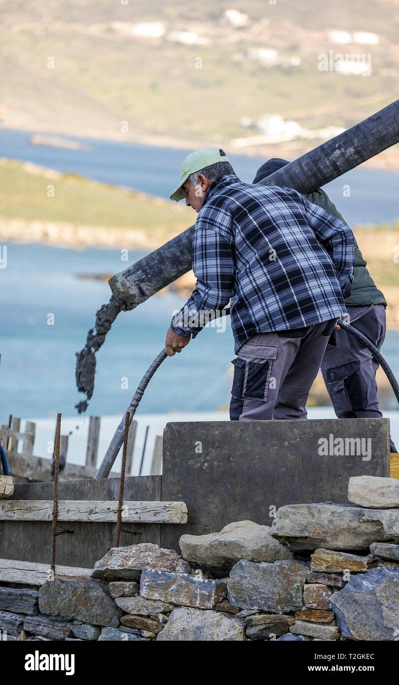 Finikas: April 2nd . Workers layinng concrete on construction site with  truck mixer concrete pump . Finikas April 2nd , Syros Greece, 2019. - Stock Image