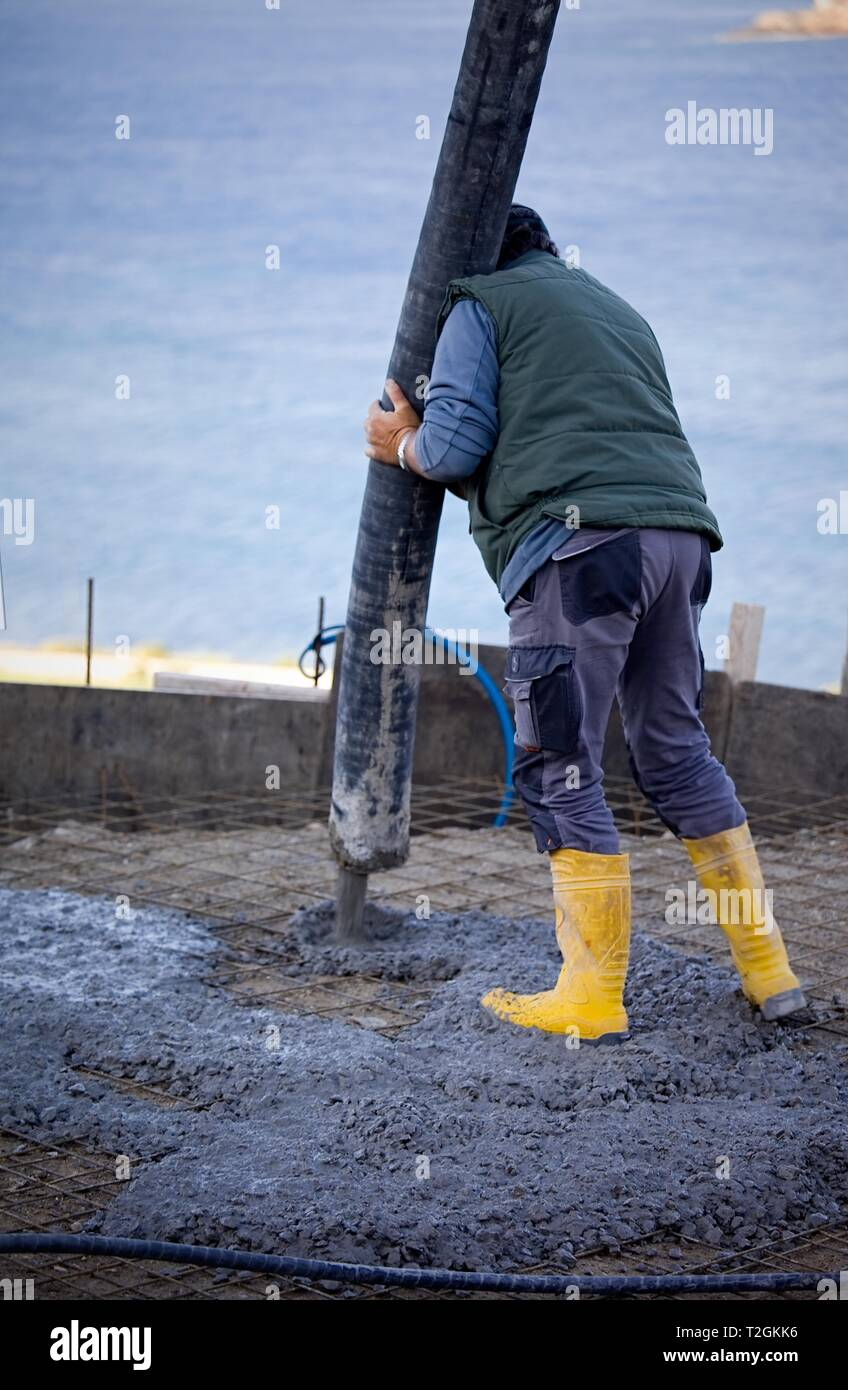 Worker laying cement on site with concrete pump. Stock Image. Stock Photo