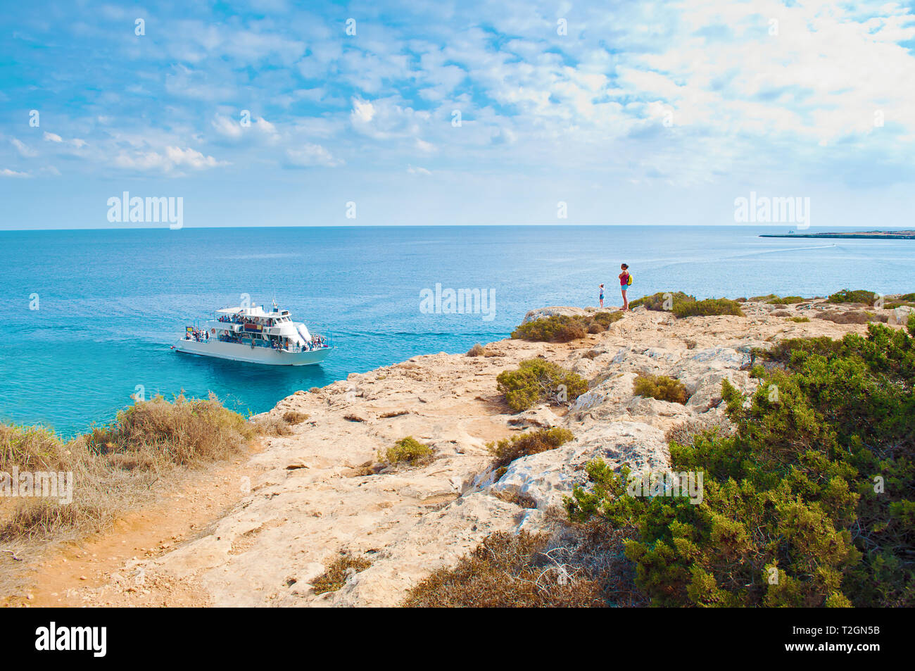 Two tiny figures of girls standing on the edge of a cliff. One white tourist ship in a bay near Cape Greco, Cyprus. Rock coastline near deep green tra Stock Photo