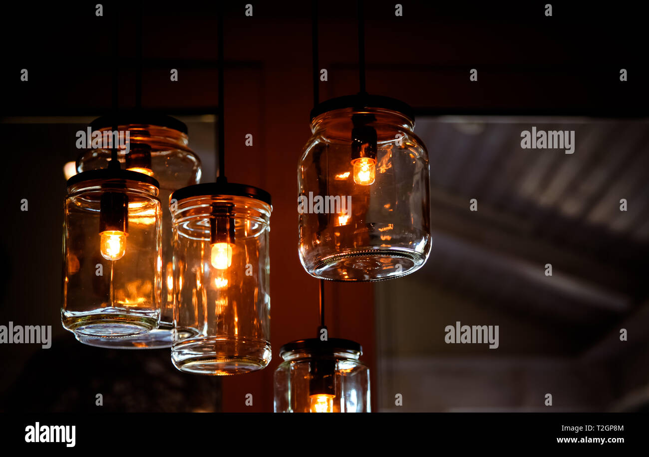 Retro vintage light bulbs inside empty DIY jar glasses as creative lamps hangings from the ceiling in house interior detail and blurred background. - Stock Image