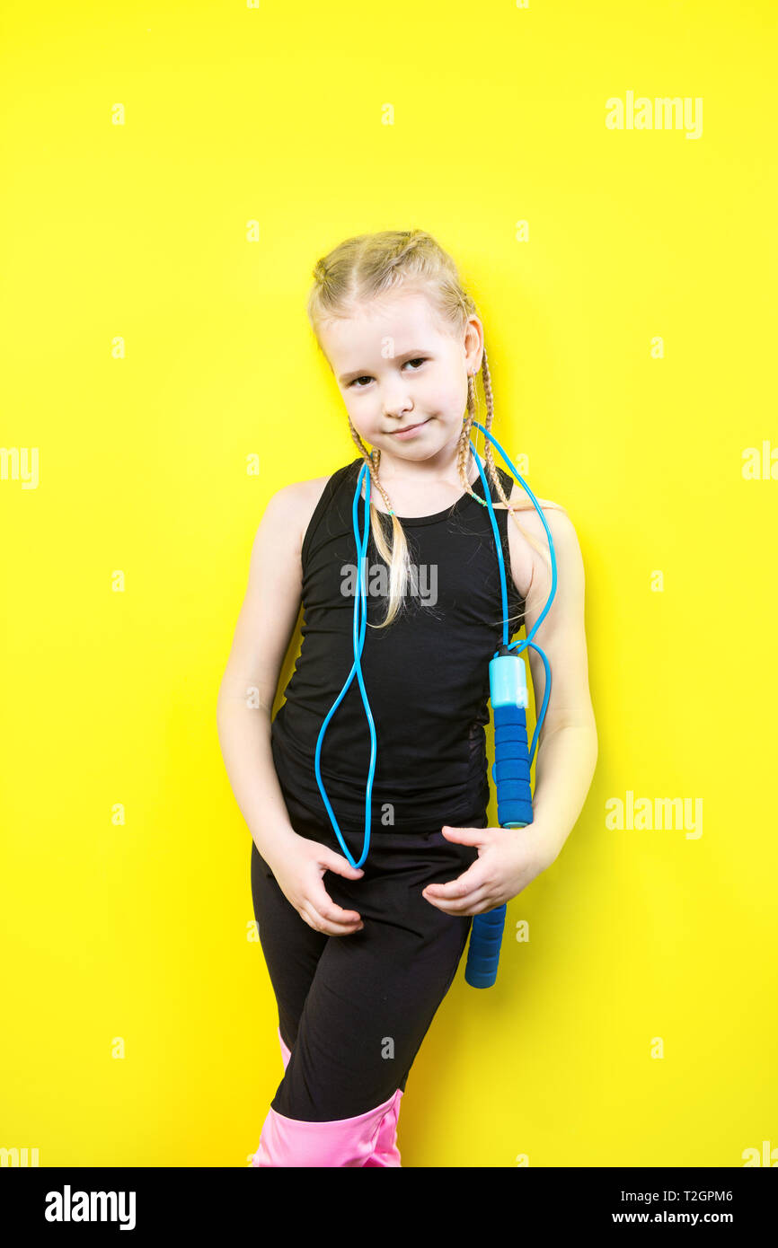 0272746d93431 Theme sport and health. Beautiful caucasian child girl with pigtails posing  yellow background with smile