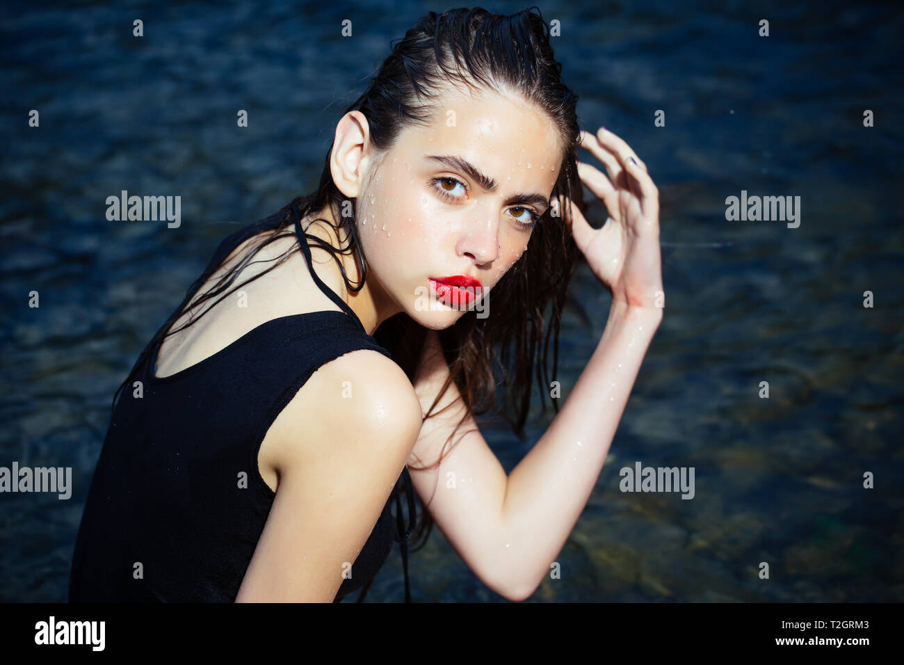 Fashion, beauty, makeup. Young woman with red lips in water. Diet, health, workout, fitness, refresh. Summer vacation, swimming, sport, diet Woman swi - Stock Image