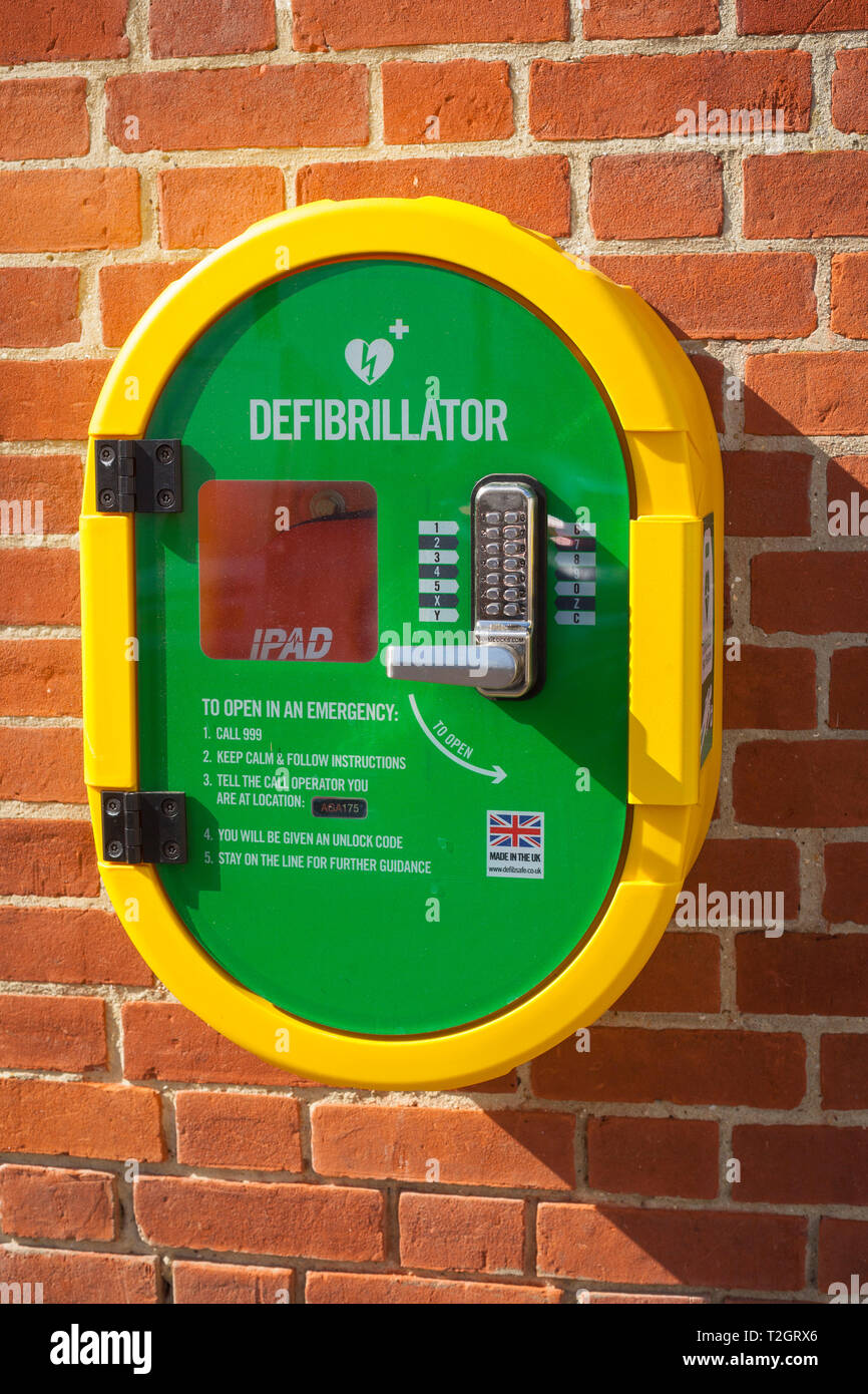 Brightly coloured yellow and green Public Access Difibrillator (PAD) on a brick wall at Henley-on-Thames Fire Station - Stock Image
