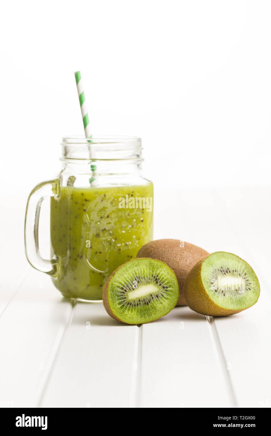 Glass of kiwi smoothie juice and kiwi fruit. - Stock Image