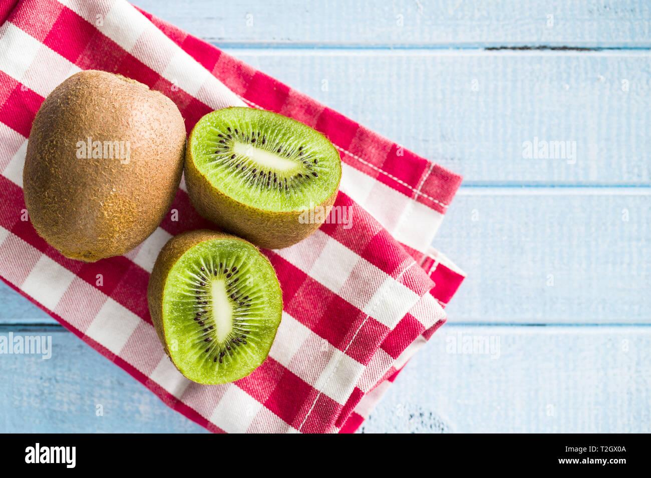 Sliced kiwi fruit on checkered napkin. Top view. - Stock Image