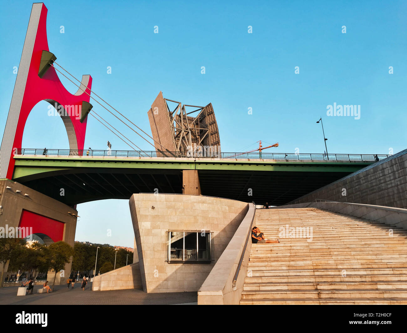 Basque country - september 11 - 2018: Couple resting at the stairs of la salve zubia bridge in the spanish city of Bilbao. Stock Photo