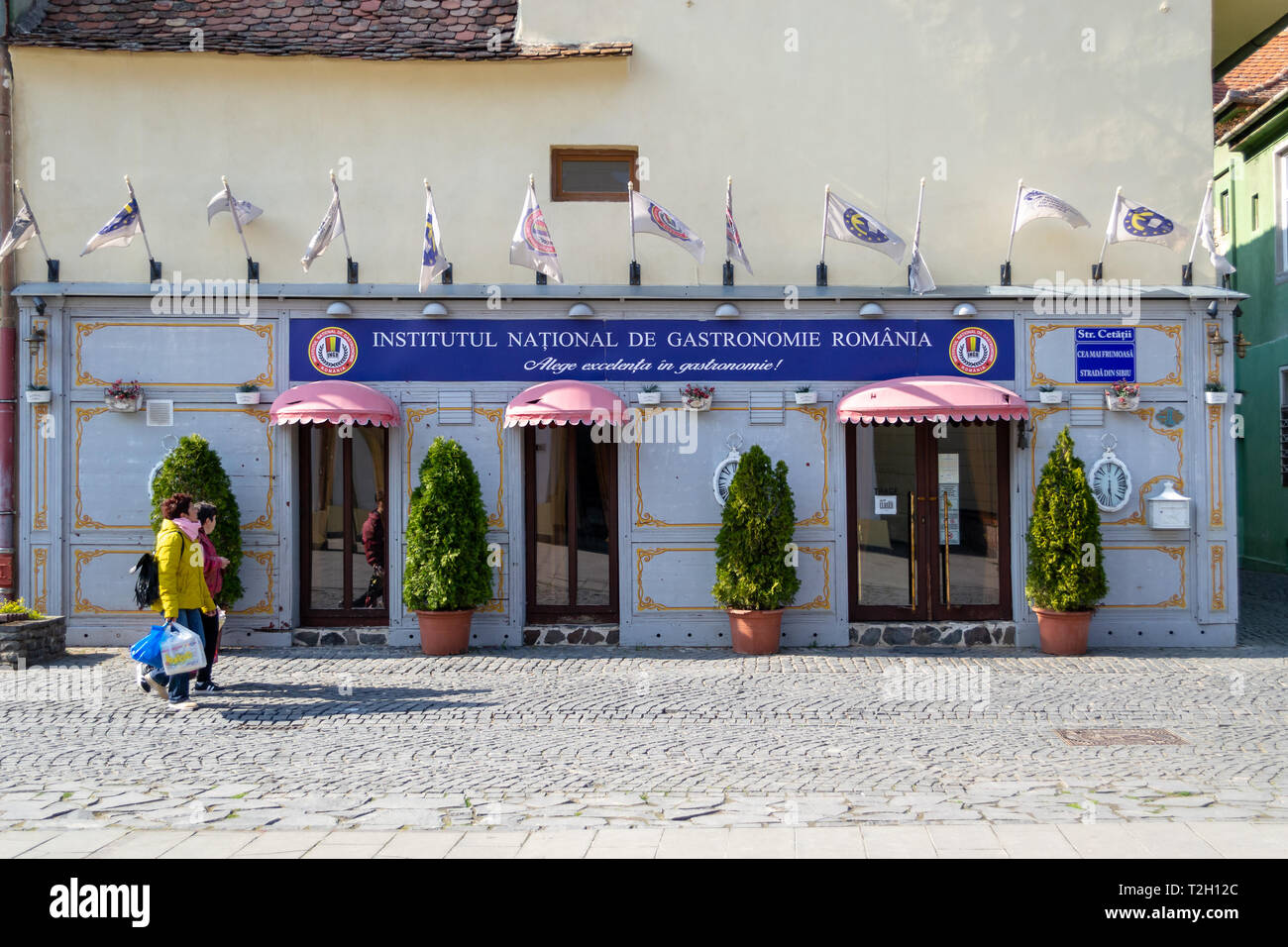 Sibiu, Romania - March 25, 2019: Front entrance and facade of 'Institutul National de Gastronomie Romania', a culinary organization that promotes trad - Stock Image