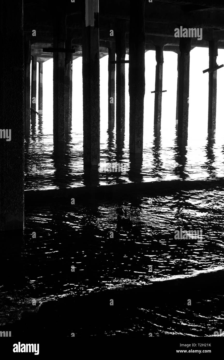 gentle waves under the pier at Walton on Naze - Stock Image