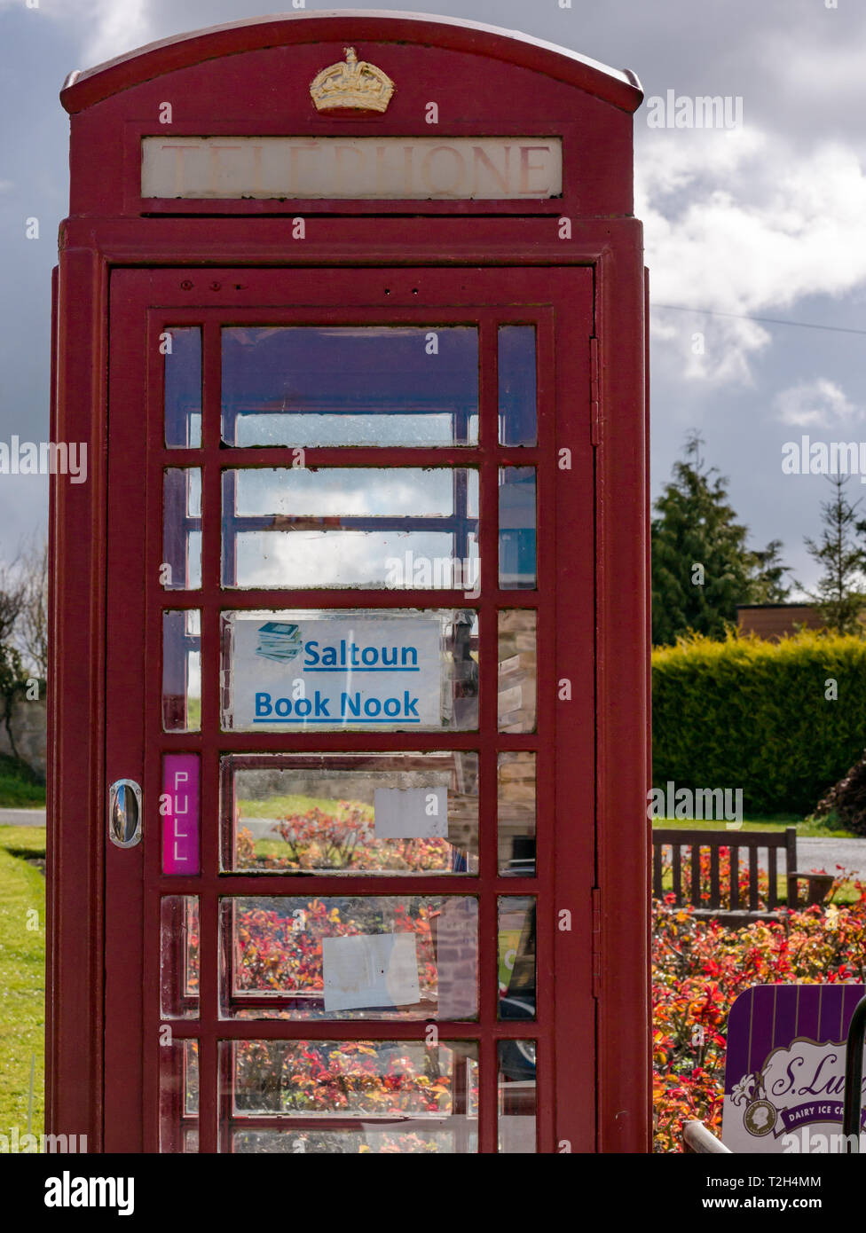 Old red telephone box converted to book lending library in conservation village, East Saltoun, East Lothian, Scotland, UK - Stock Image