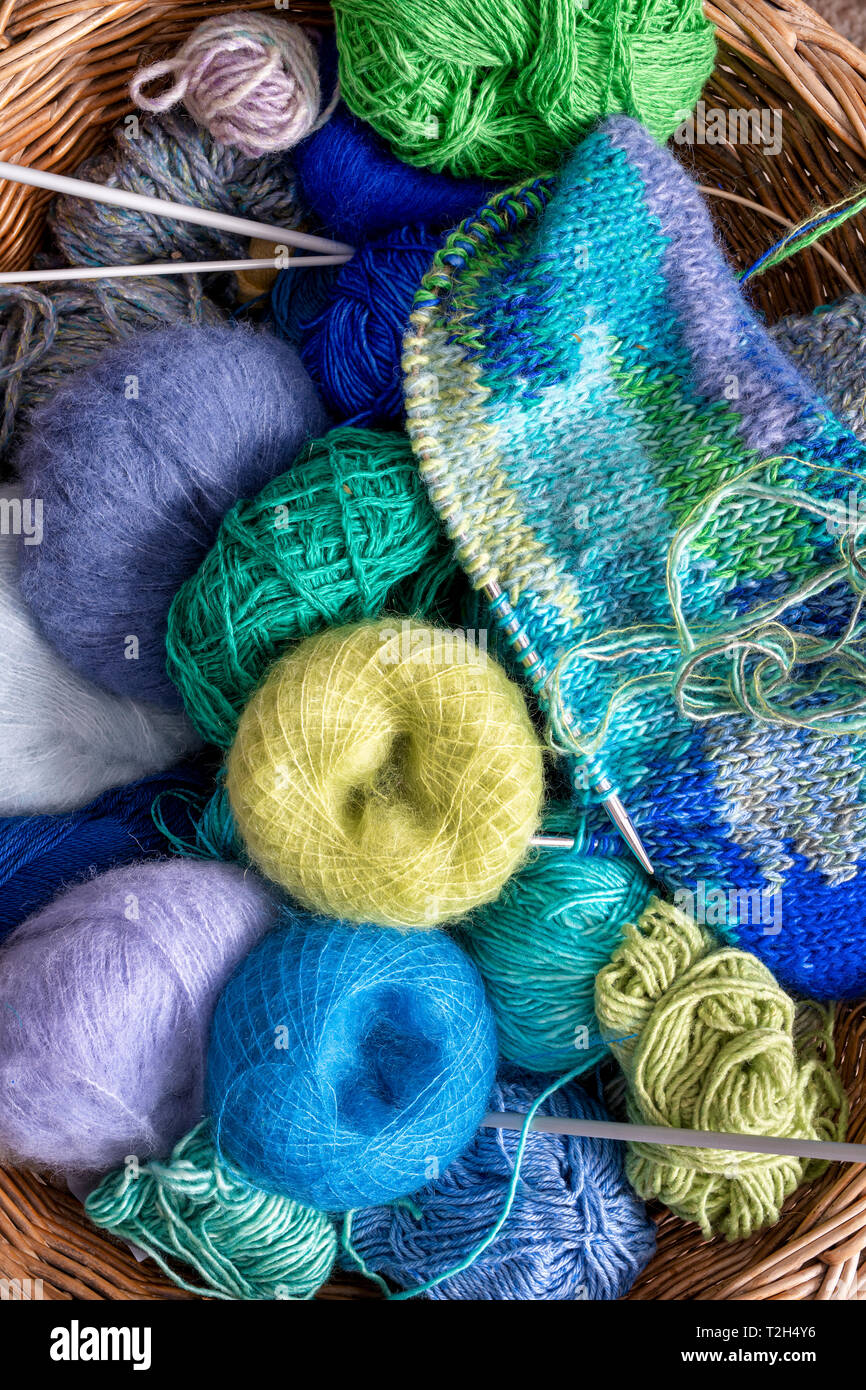 Balls of colourful wool in a knitting basket Stock Photo