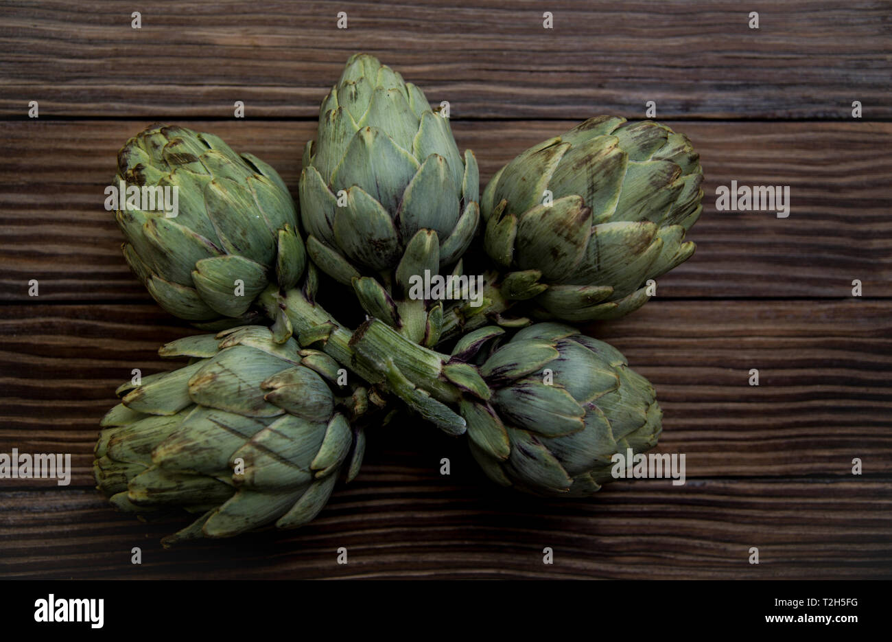 artichokes on old wooden table Stock Photo