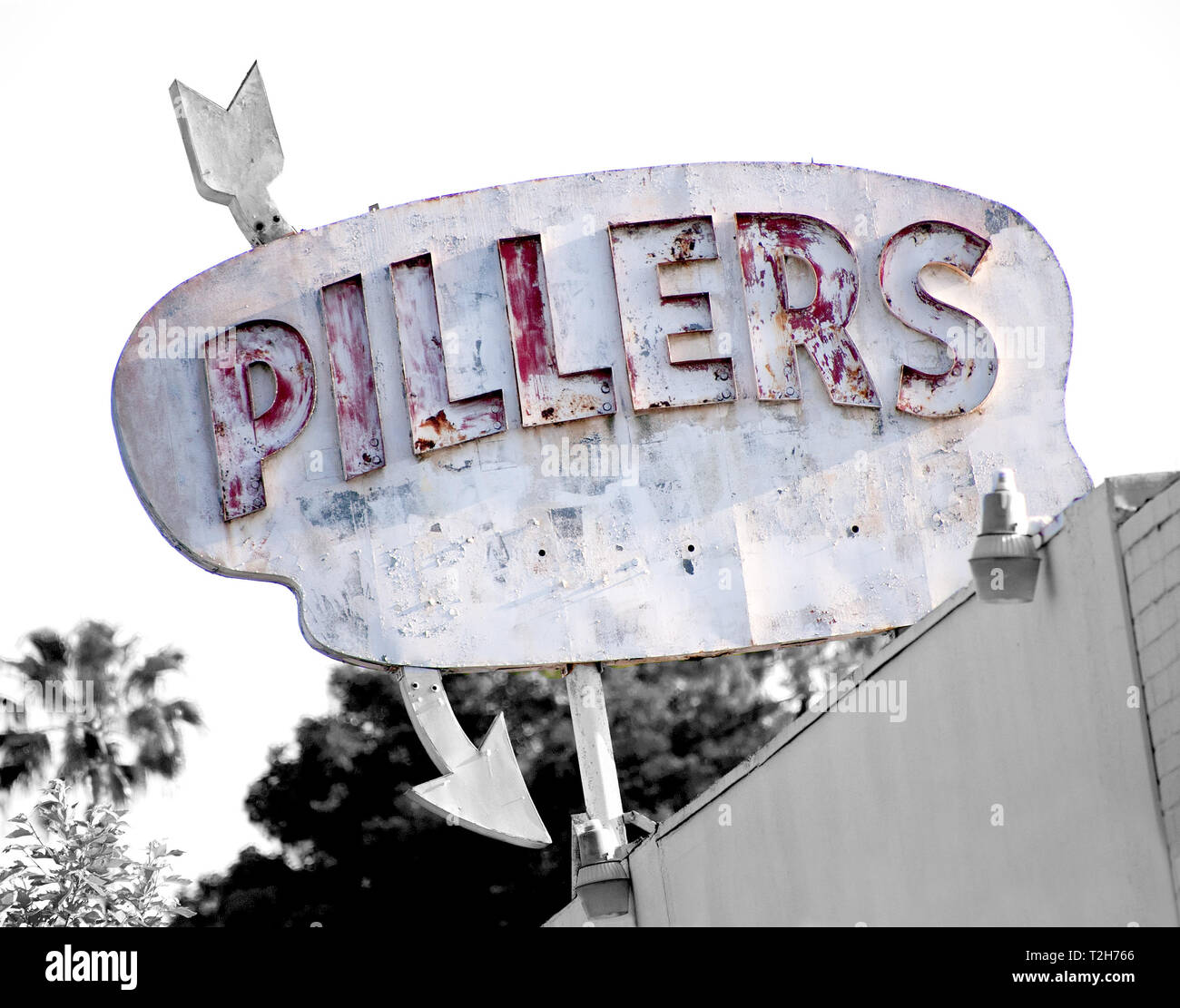 This old wooden sign was found on an unknown building in Eagle Rock CA.  It is distressed and rather shabby.  It has raised red letters and an arrow. - Stock Image