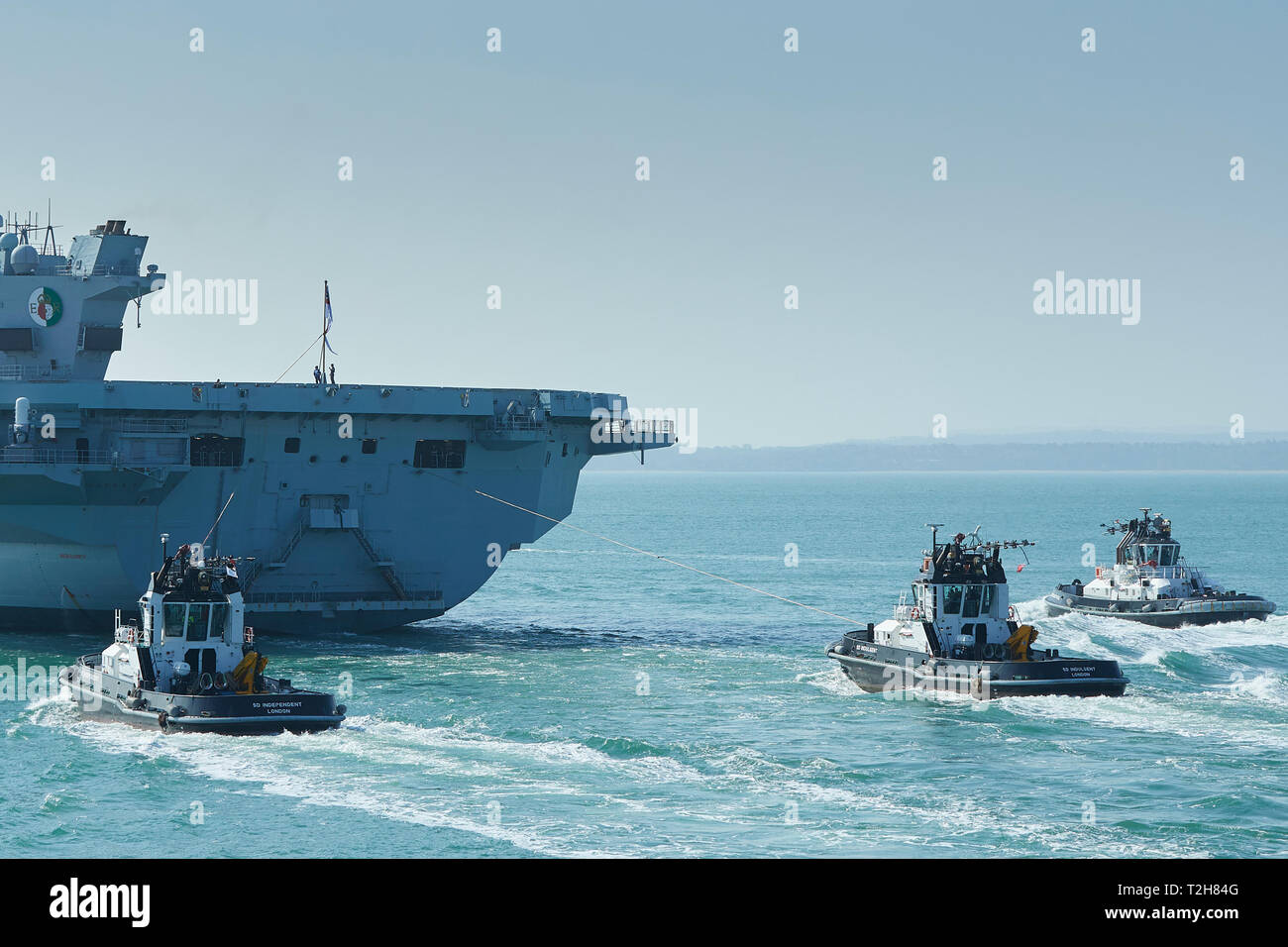 The Royal Navy Aircraft Carrier, HMS QUEEN ELIZABETH, Being Assisted By 3 Tugs At The Stern, As She Departs Portsmouth For Rosyth. 01 April 2019. - Stock Image