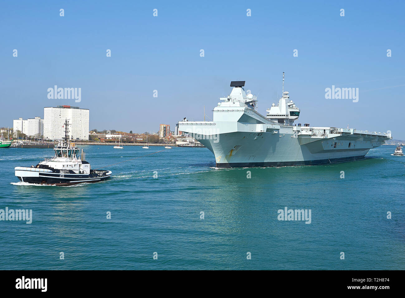The Royal Navy Aircraft Carrier, HMS QUEEN ELIZABETH, Being Assisted Tug, SD TEMPEST, As She Departs Portsmouth For Rosyth, Scotland. 01 April 2019. - Stock Image