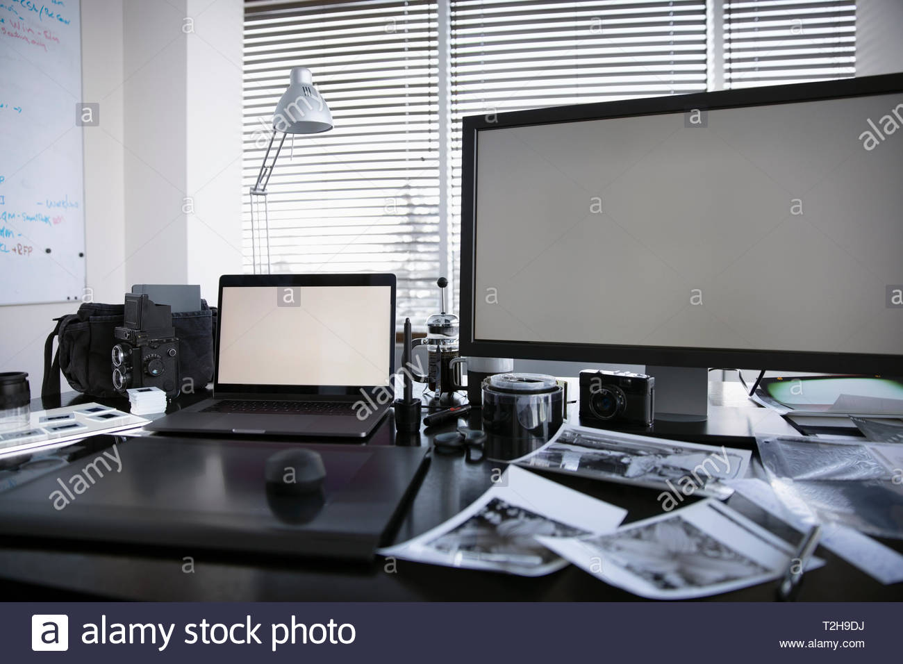 Computers and photography equipment, negatives on desk - Stock Image