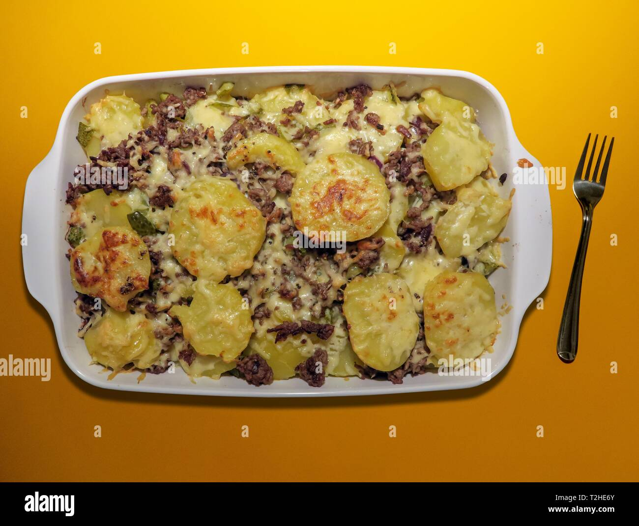 Casserole, potato casserole with minced meat, home cooking, orange background, fork, Germany - Stock Image
