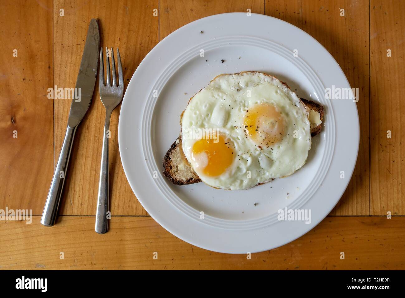 Strammer Max, two fried eggs on bread, white plate, wooden table, cutlery, knife and fork, home cooking, German cuisine, Germany - Stock Image
