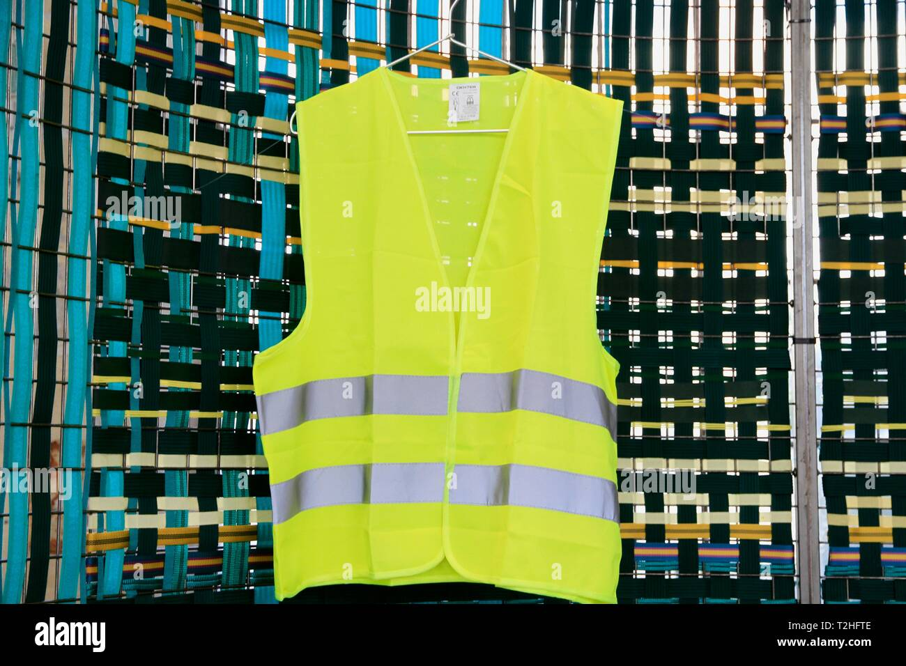 Yellow vest exhibited at the biennale of design. Saint Etienne, Loire, Auvergne Rhone Alpes. Saint-Etienne, FRANCE - 04/01/2019     Gilet jaune expose - Stock Image