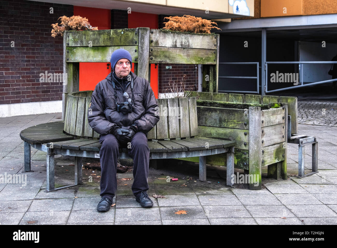 Elderly man with camera rests on a bench in Moabit, Berlin. Rustic wooden bench with plant pots - Stock Image