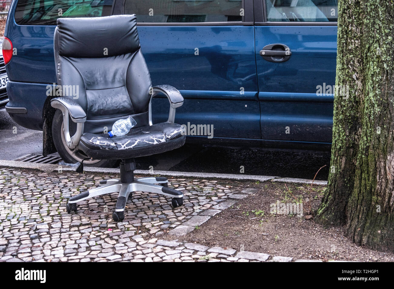 Abandoned,dumped,trashed.,discarded, redundant. Black desk chair on a pavement in Berlin - Stock Image