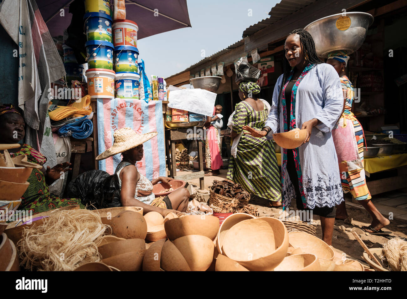 Woman choosing wooden bowl at market stall in Accra, Ghana, Africa - Stock Image