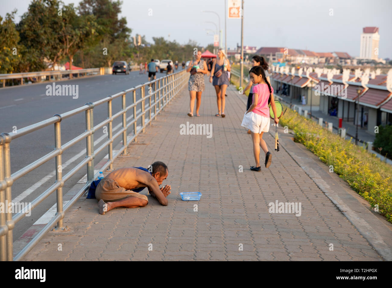 Beggar on pavement opposite the Chao Anouvong Park, Vientiane, Laos, Southeast Asia - Stock Image
