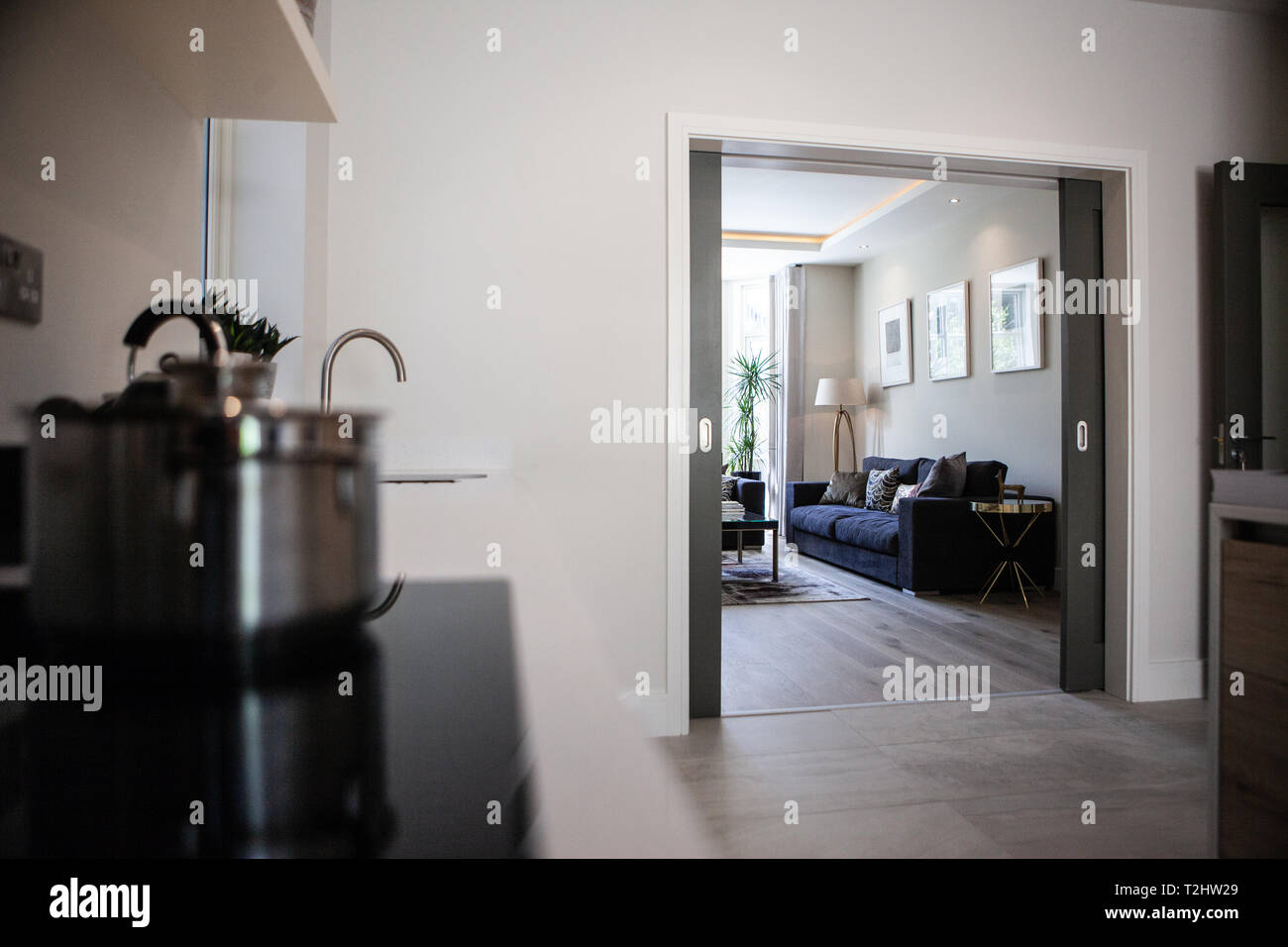 kitchen area showing inter connected rooms to family room in front of house through double doors. - Stock Image