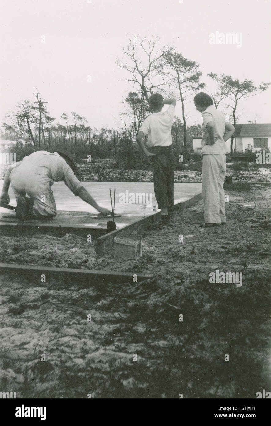 Antique c1950 photograph, man using a concrete float on new foundation poured in a frame. Location unknown, USA. SOURCE: ORIGINAL PHOTOGRAPHIC PRINT. African-American; blacksmith; black; man; shoe; shoeing; horse; farrier; cleaning; horseshoe; barn; anvil; handyman; photo; photograph; antique; vintage; period; old; candid; snapshot; historic; historical; archival; archive; b&w; black and white; 20th century; twentieth century; 1900s; 1950s; 1960s; 1950 - Stock Image