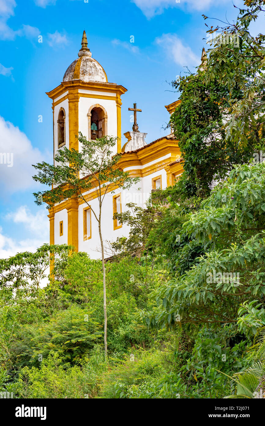 Old catholic church of the 18th century located in the center of the famous and historical city of Ouro Preto in Minas Gerais between vegetation - Stock Image