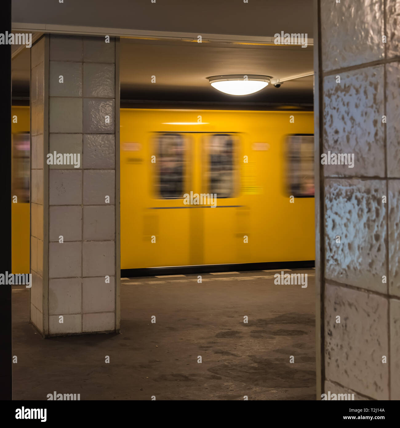 The old yellow berlin subway moves swiftly into the subway station - Stock Image