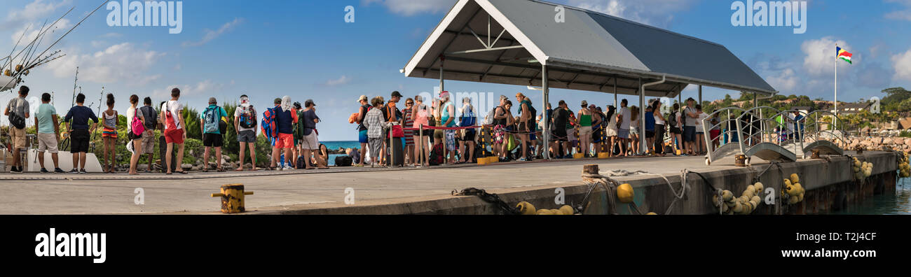 La Dique, Seychelles - February 4th, 2019: Queue of people waiting to embark at the Pier of La Digue, Seychelles. - Stock Image