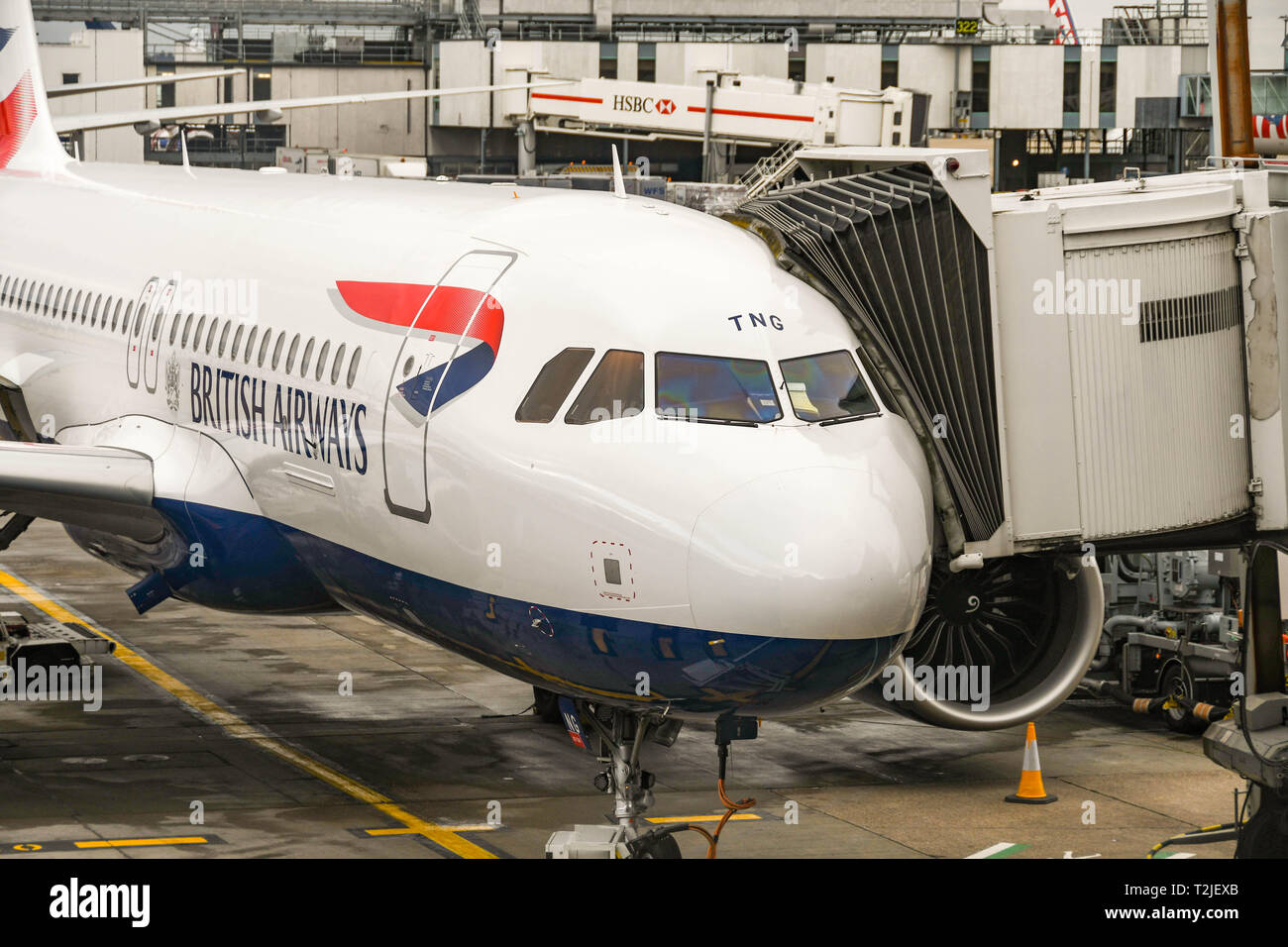 LONDON HEATHROW AIRPORT, ENGLAND - FEBRUARY 2019:  New British Airways Airbus A320 Neo short-haul jet attached to a passenger jettty - Stock Image