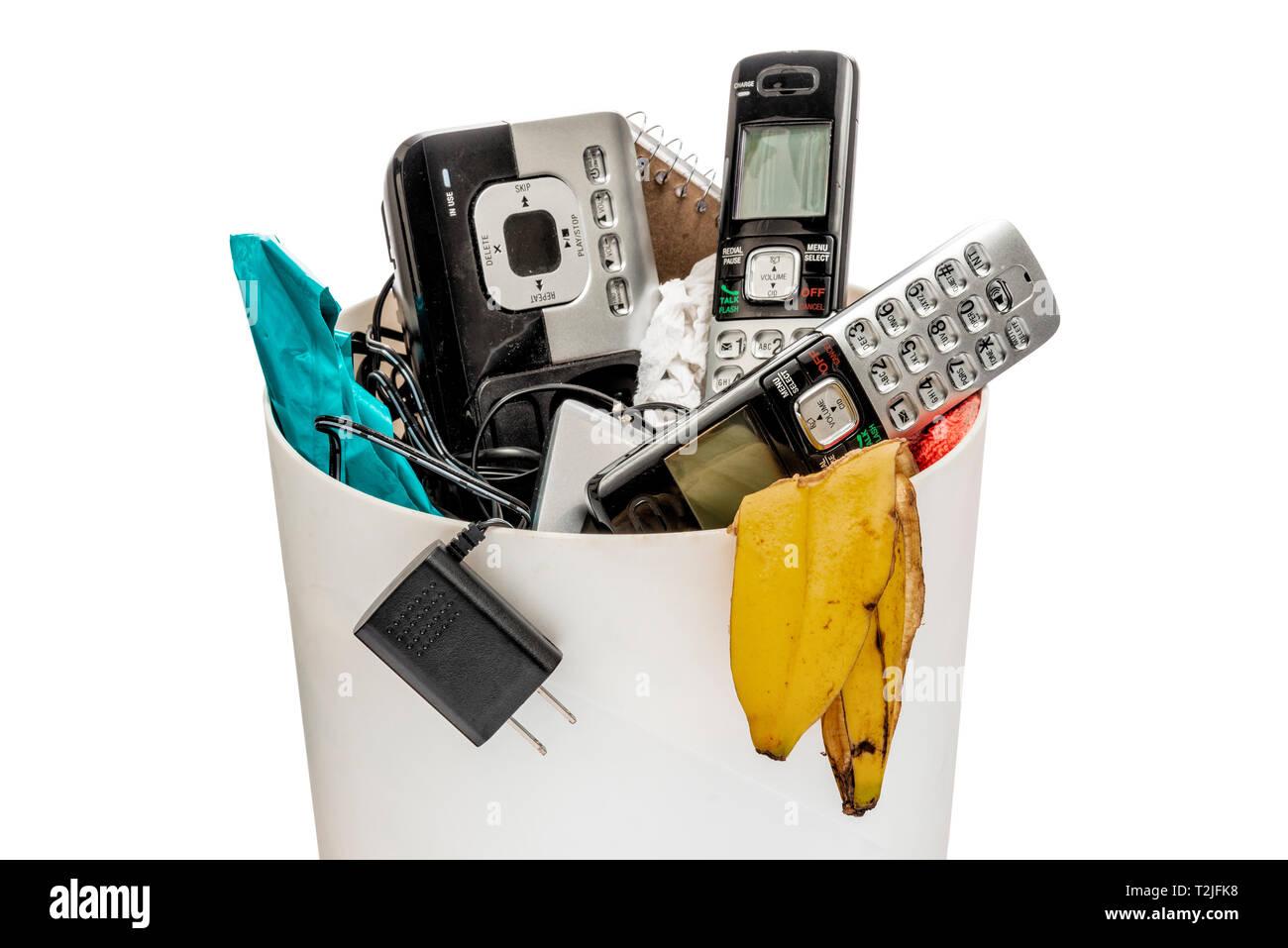 Horizontal shot of land line telephones thrown away in a trashcan. - Stock Image