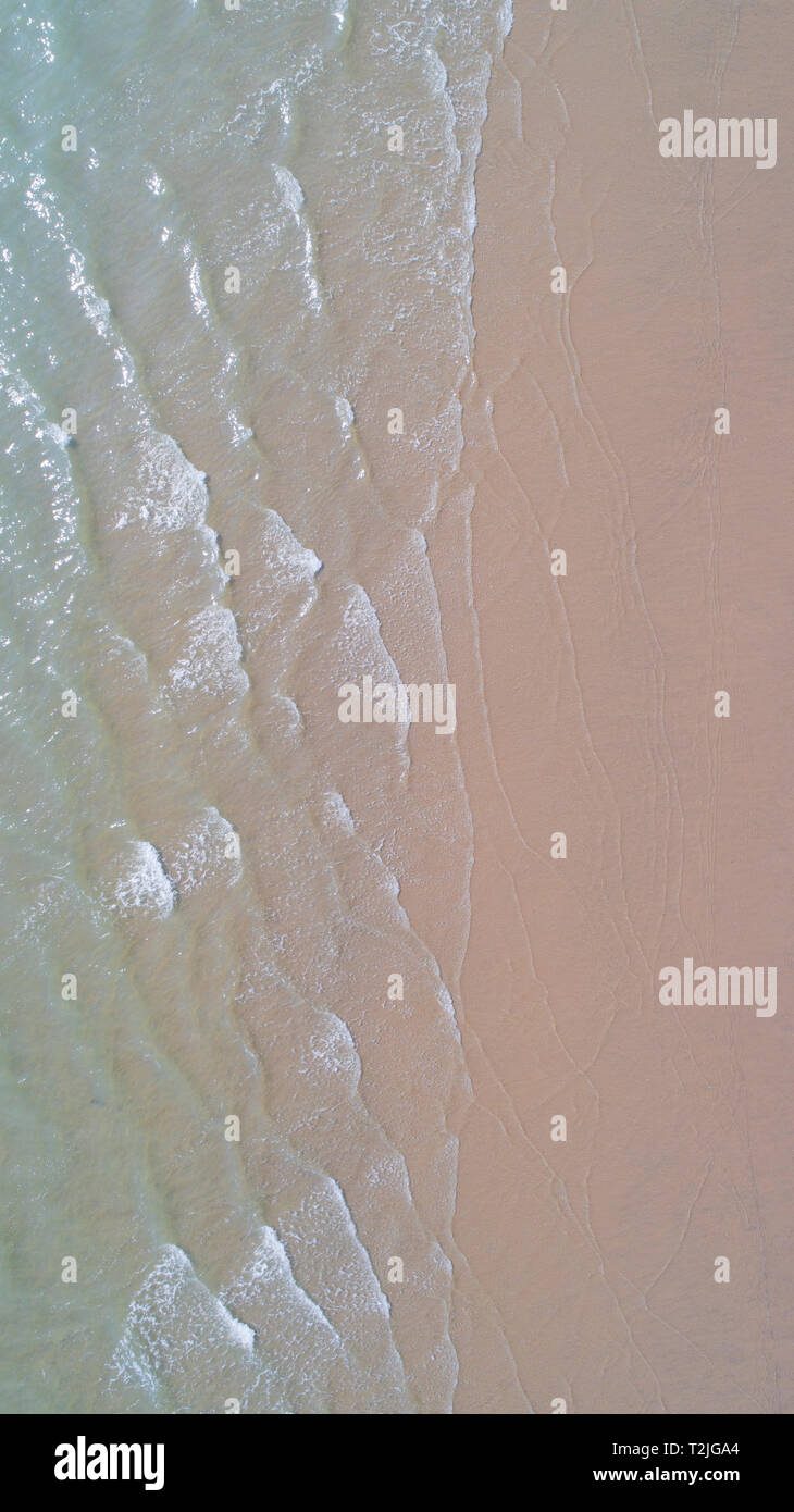 Gentle surf laps a sandy beach, seen from above, Sussex, UK - Stock Image