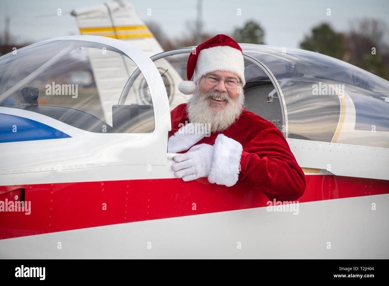 Santa leans out of side of private aircraft and lets out a smile, Tangier, Virginia - Stock Image