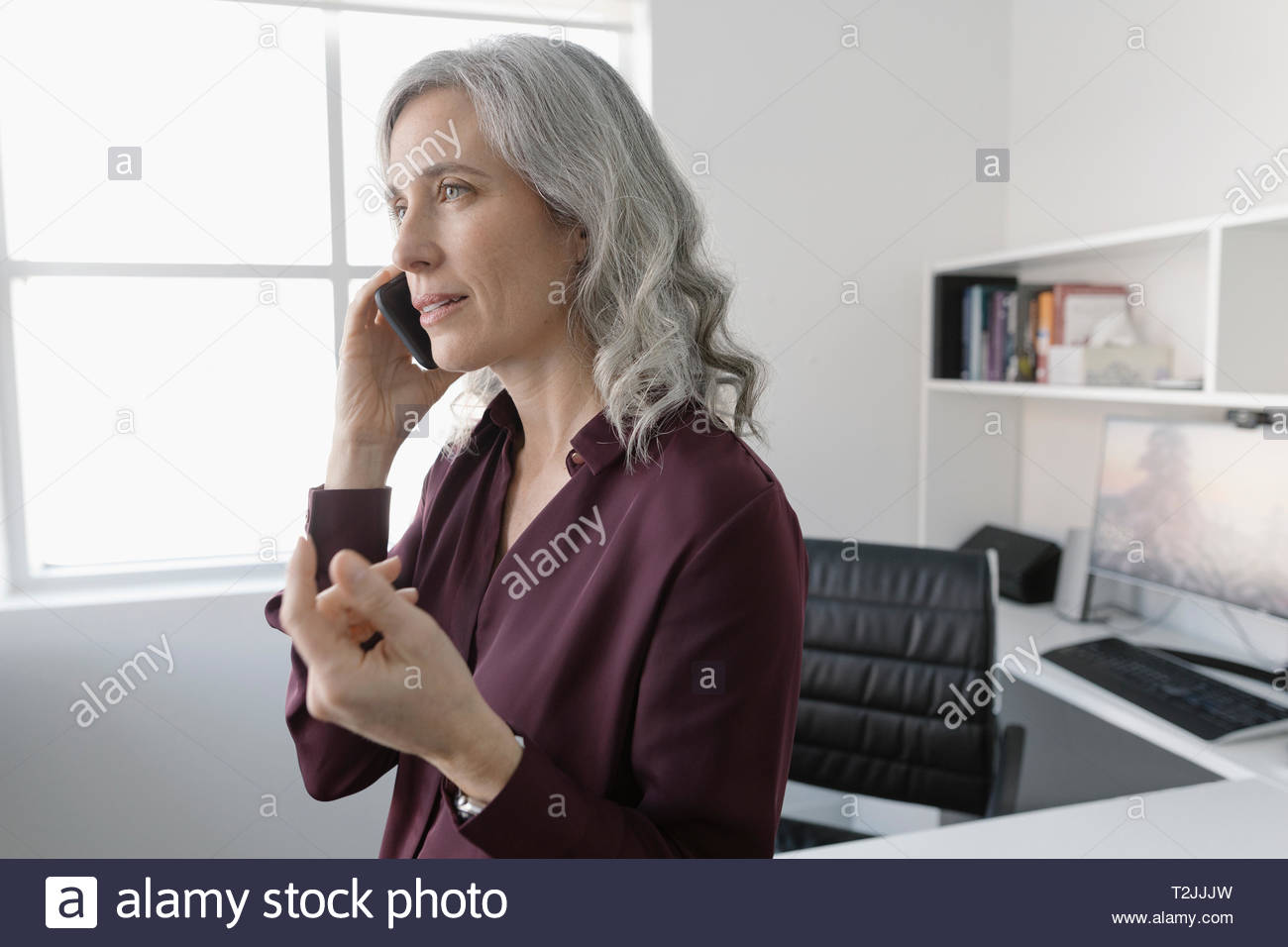 Businesswoman talking on cell phone in office - Stock Image