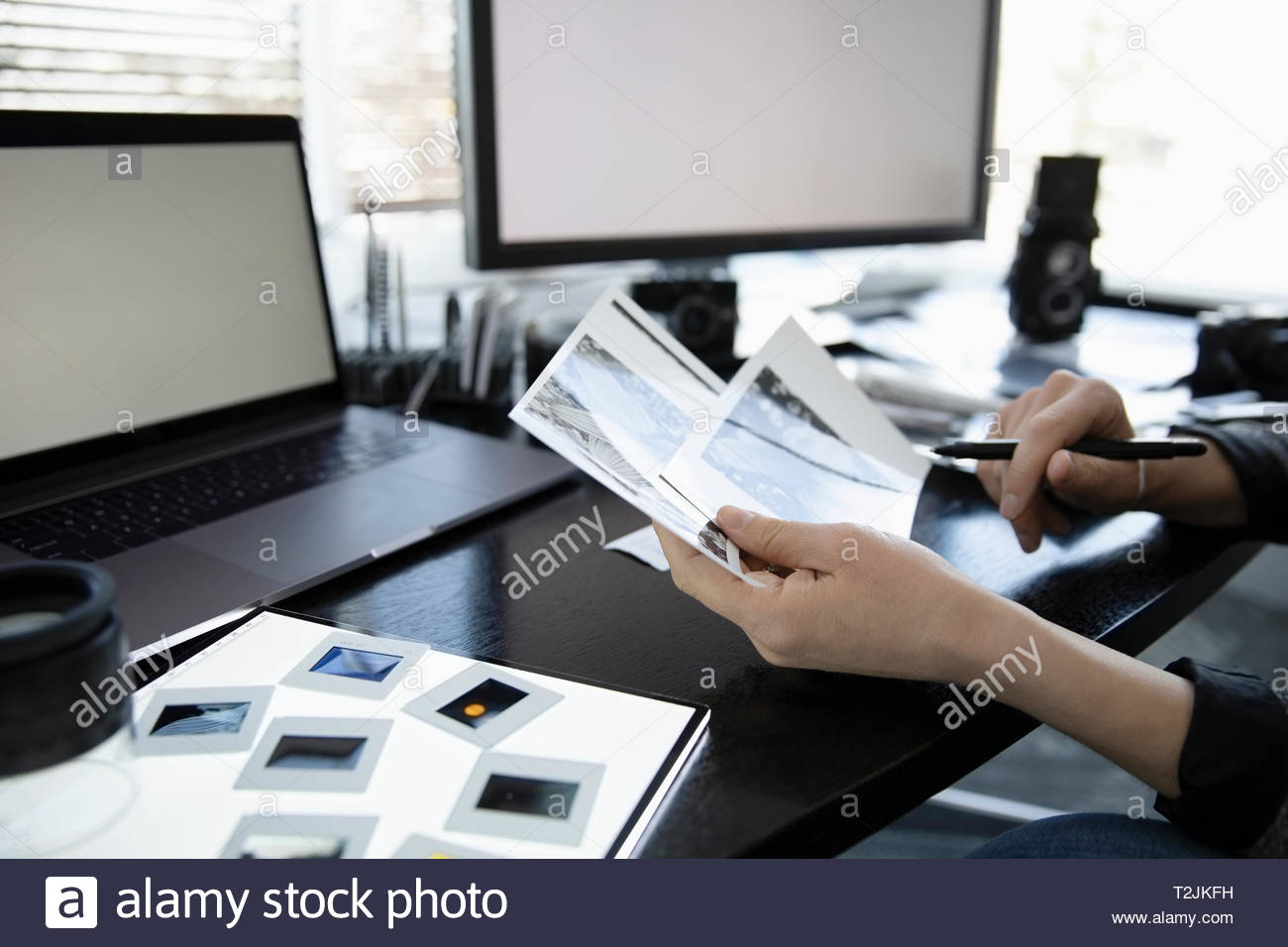 Photographer reviewing photograph negatives at desk - Stock Image