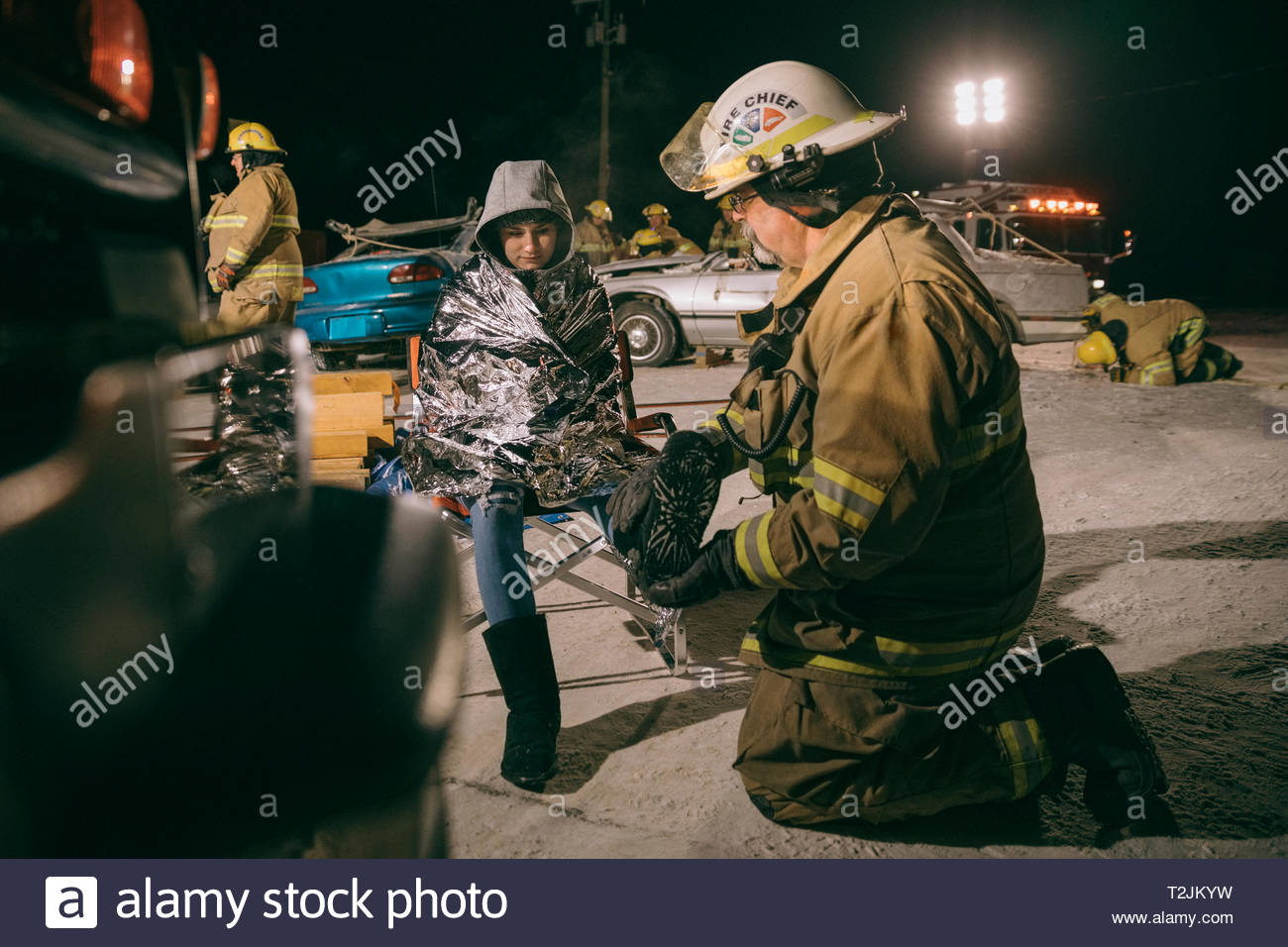 Firefighter tending to car accident victim - Stock Image