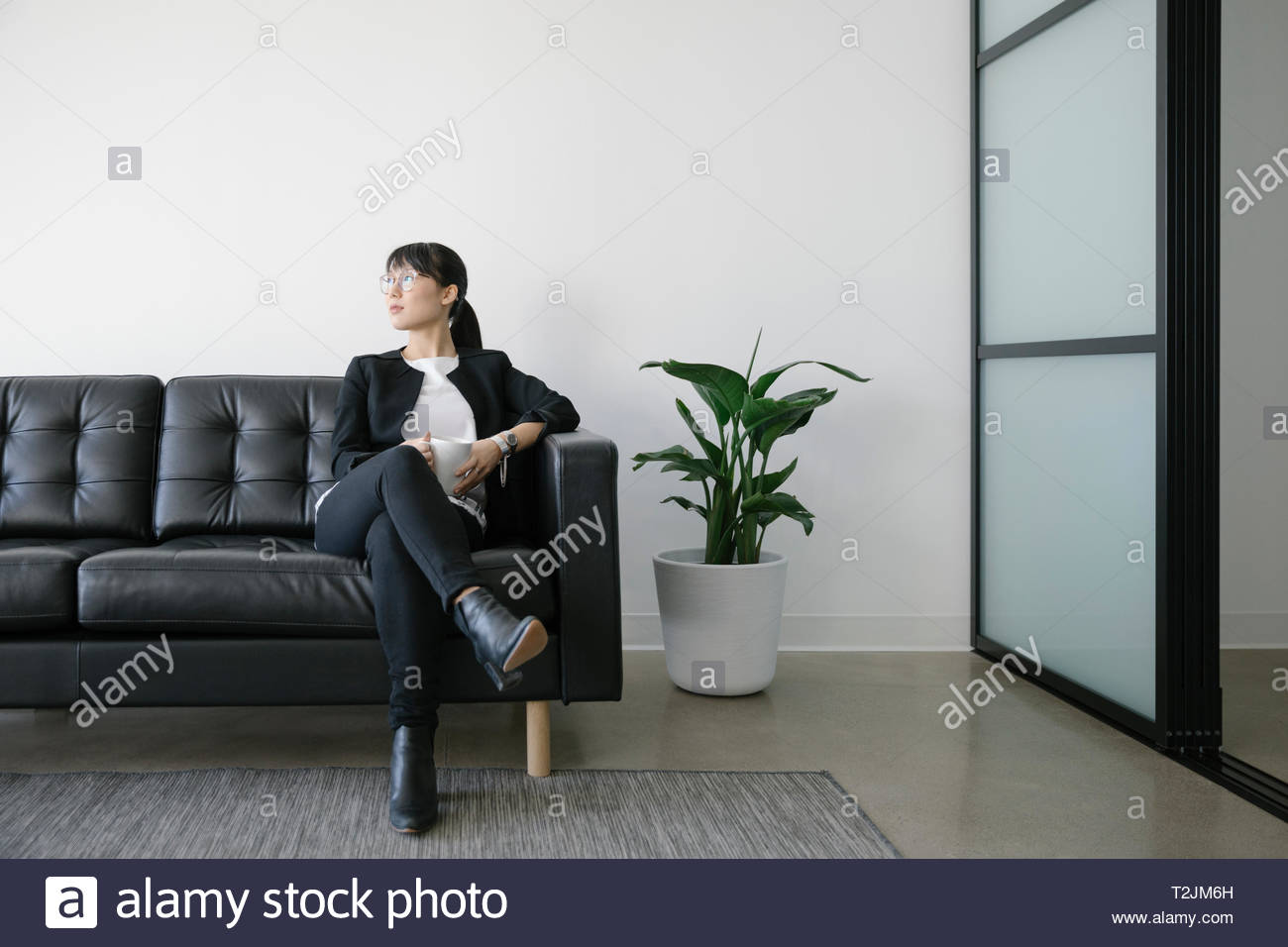 Thoughtful businesswoman with coffee on leather sofa - Stock Image