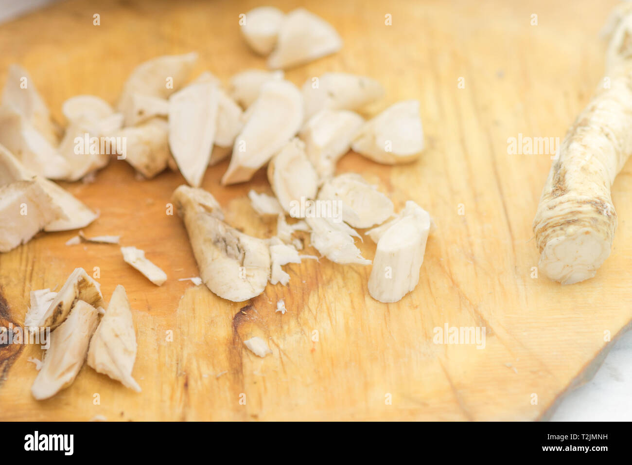 Horseradish root sliced on the board. Top view. - Stock Image