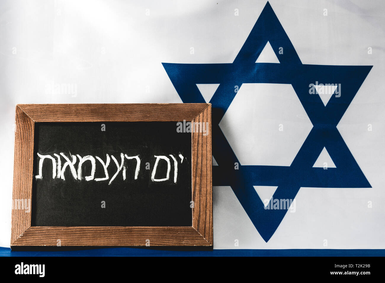 chalkboard with hebrew lettering near blue star of david on national flag of israel - Stock Image