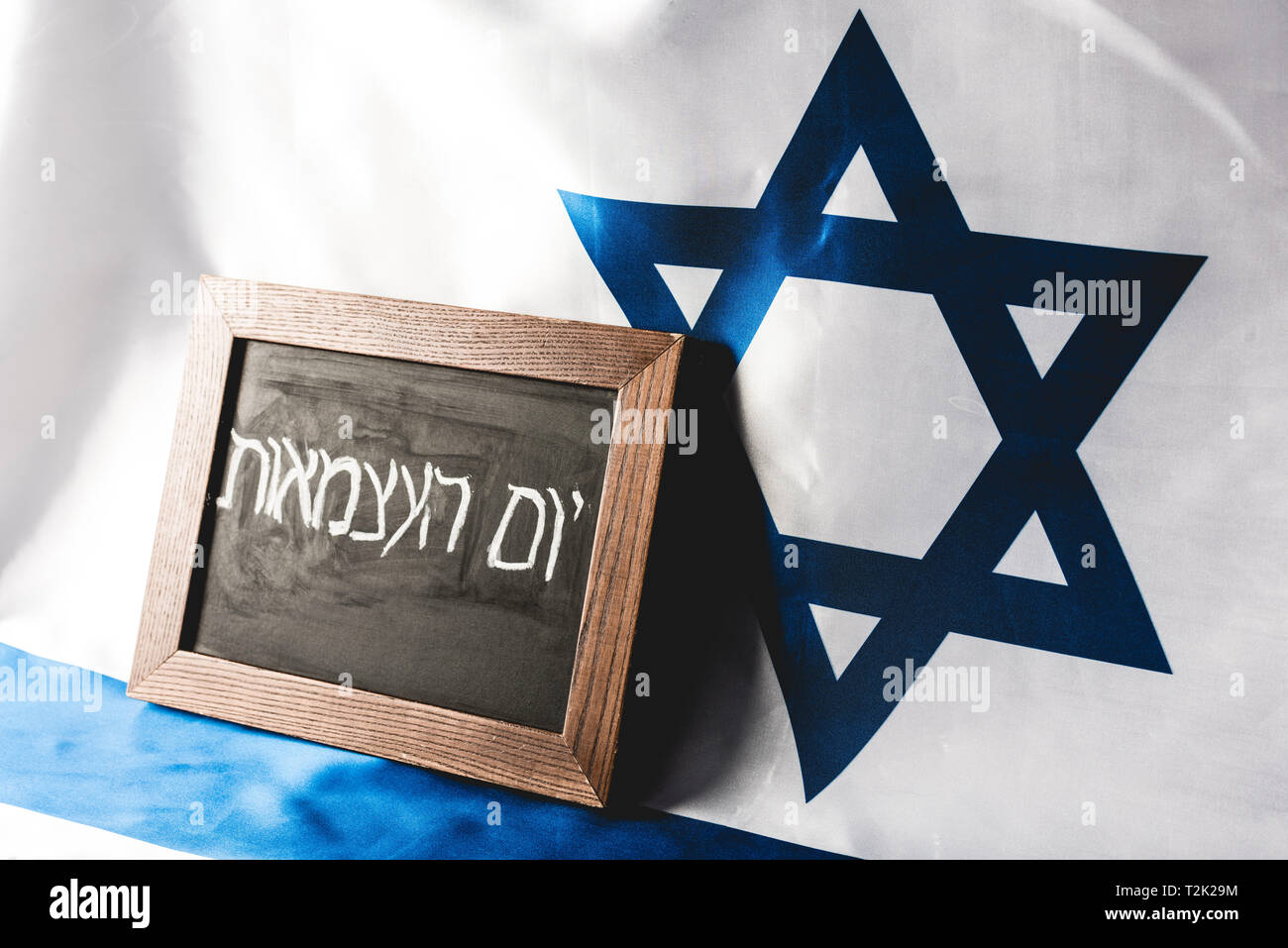 chalkboard with hebrew lettering near national flag of israel - Stock Image