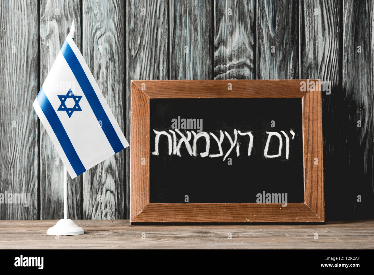 chalkboard with hebrew lettering near national flag of israel with blue star of david - Stock Image