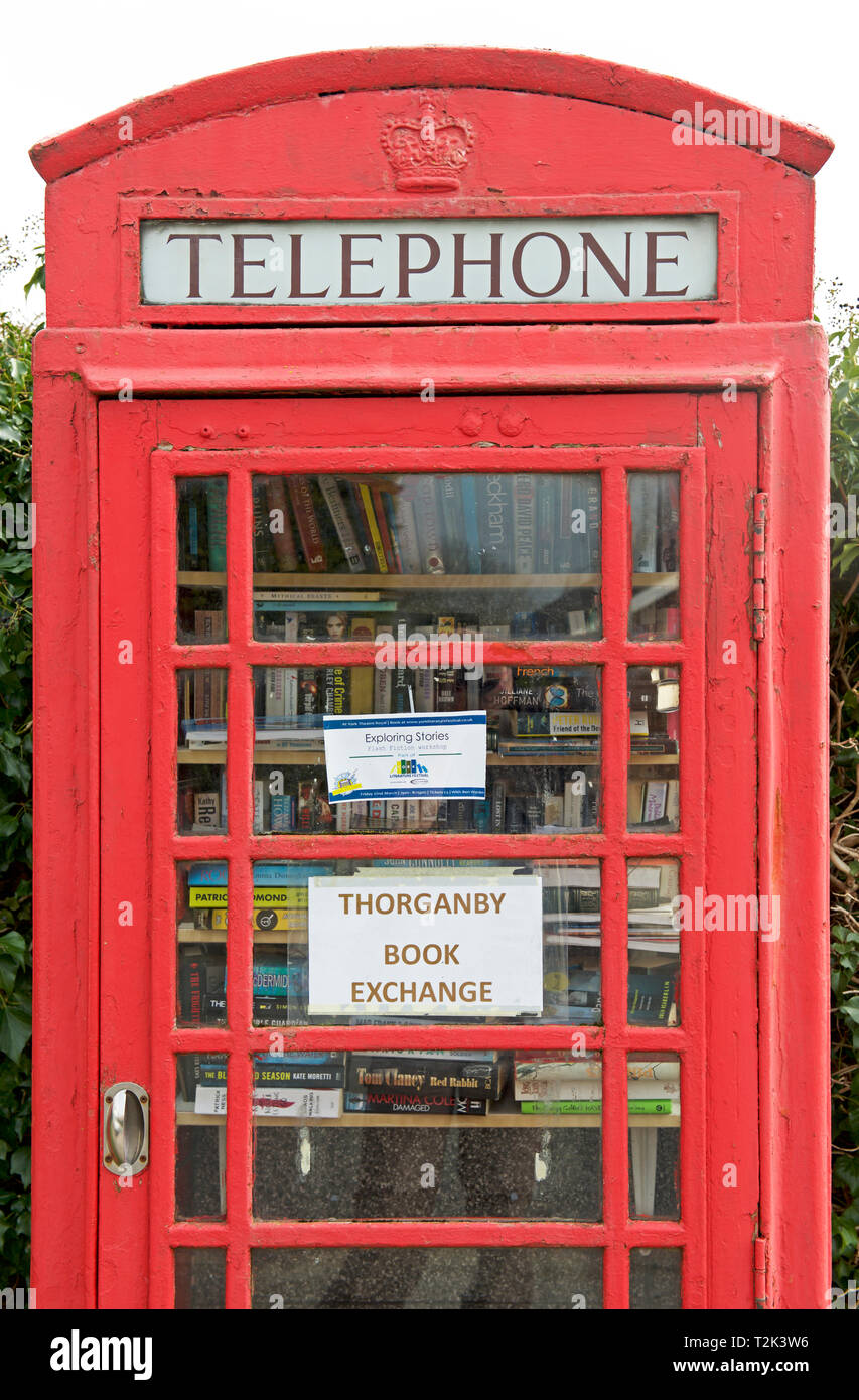 Redundant telephone box used as a lending library in the village of Thorganby, East Yorkshire, England UK - Stock Image